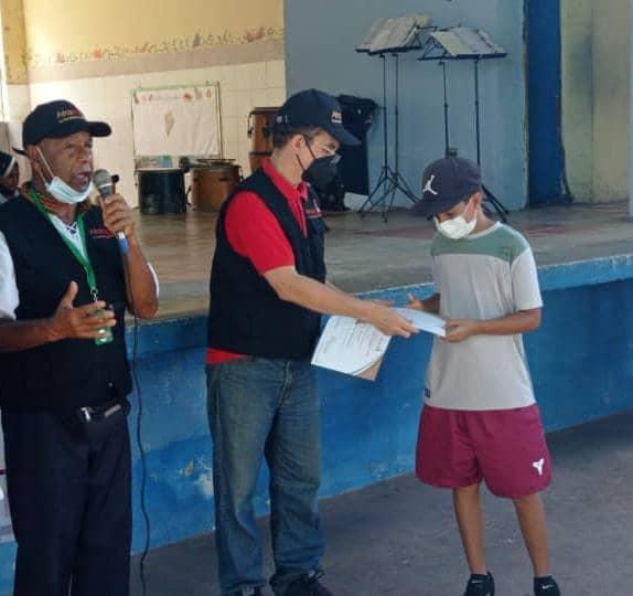 Un adolescentes recibe su diploma de manos de Reinaldo Bolívar